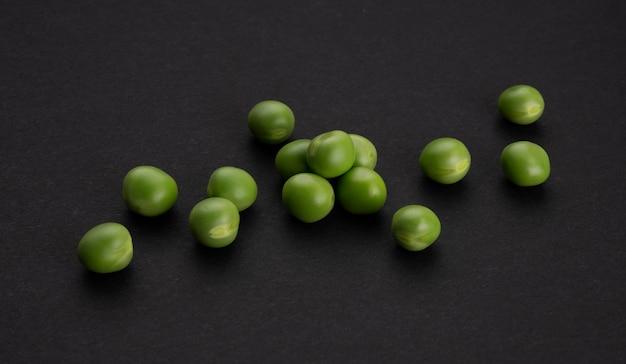 Frische grüne erbsen auf schwarzem hintergrund, draufsicht