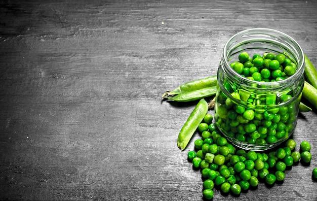 Frische grüne erbsen im glas. auf der schwarzen tafel.