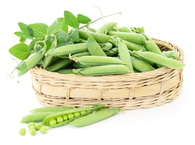Frische grüne erbsen im korb auf einem weißen