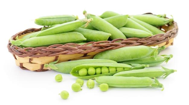 Frische grüne erbsen im korb auf weiß.