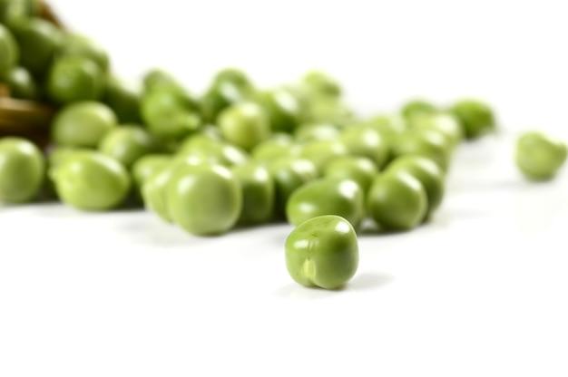 Frische grüne erbsen im korb auf weißem hintergrund