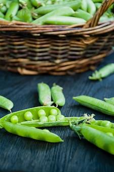 Frische grüne erbsen in einem strohkorb.