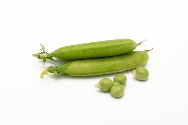 Frische grüne erbsenschote mit samen auf einem weißen hintergrund