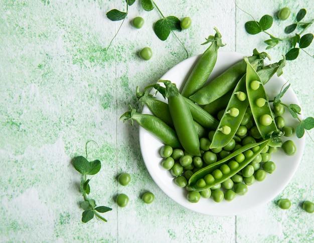 Frische grüne erbsenschoten und grüne erbsen mit sprossen auf grünem holzhintergrund. konzept der gesunden ernährung, frisches gemüse.