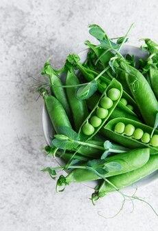 Frische grüne erbsenschoten und grüne erbsen mit sprossen auf konkretem hintergrund. konzept der gesunden ernährung, frisches gemüse.