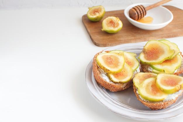 Frische grüne feigen holzbrett porzellanteller vollkornbrot honig