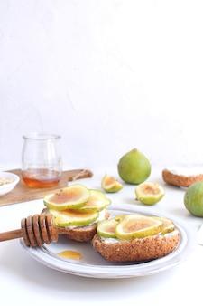 Frische grüne feigen porzellanteller vollkornbrot honig ziegenkäse