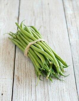 Frische grüne grüne bohnen auf einem holztisch schließen oben