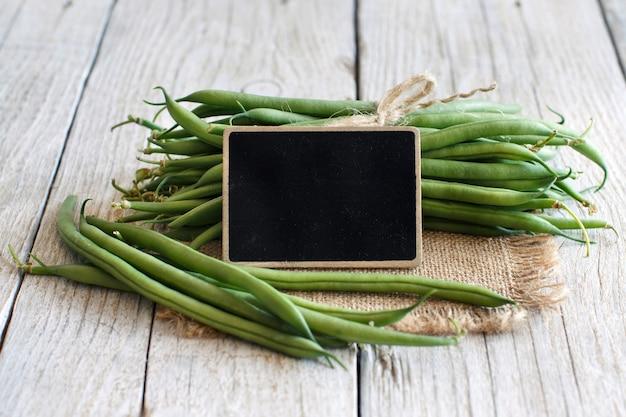 Frische grüne grüne bohnen mit einer kleinen tafel auf einem holztisch schließen oben