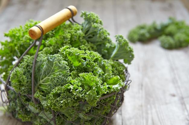 Frische grüne grünkohlblätter auf holztisch
