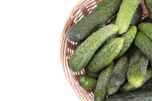 Frische grüne gurken in einem korb auf einem weißen, isolierten hintergrund. frisches gemüse. sicht von oben