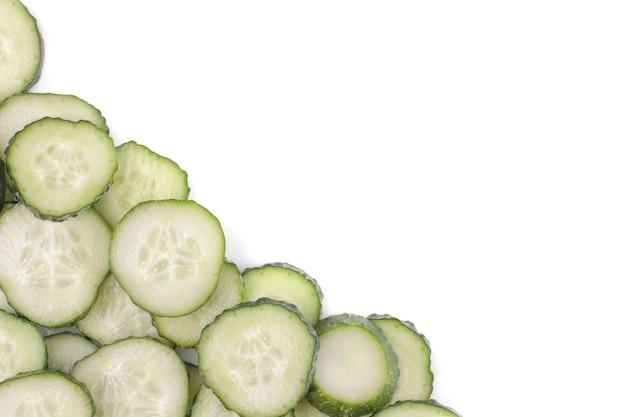 Frische grüne gurken in scheiben geschnitten auf weißem hintergrund isoliert. frisches gemüse. sicht von oben