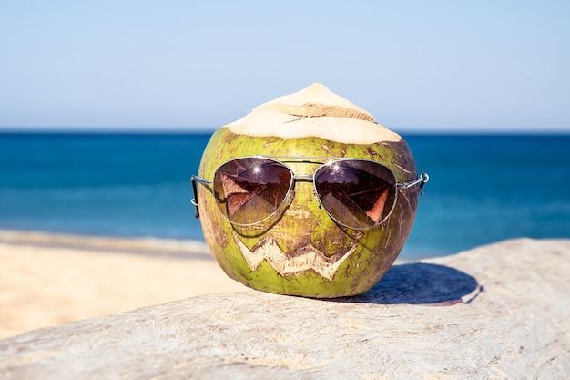 Frische grüne kokosnuss in der sonnenbrille ist symbol für halloween liegt auf baum mit geschnitztem gesicht wie kürbis
