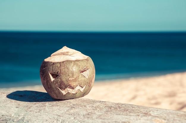 Frische grüne kokosnuss ist ein symbol für halloween liegt auf einem baum mit einem geschnitzten gesicht wie ein kürbis
