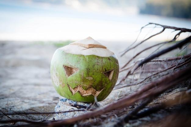 Frische grüne kokosnuss ist ein symbol für halloween mit einem geschnitzten gesicht auf kürbis liegt in wurzeln am strand