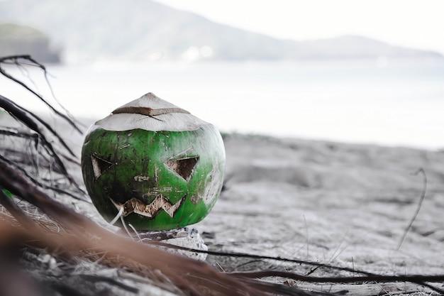 Frische grüne kokosnuss ist symbol für halloween mit geschnitztem gesicht breiter sandstrand grün-weiß getönt