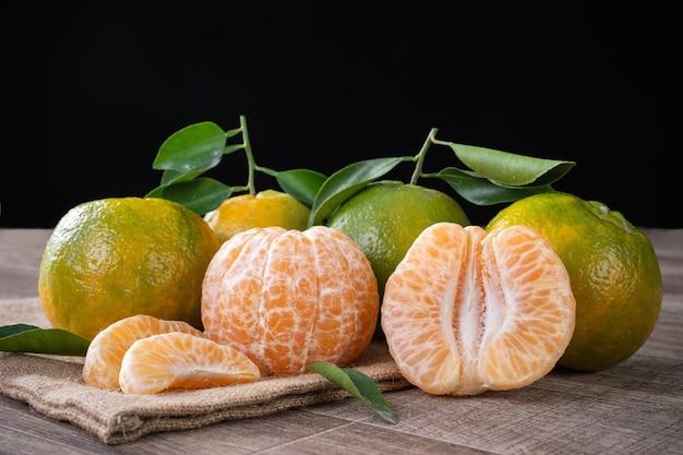 Frische grüne mandarinen-mandarine mit frischen blättern auf dunklem holztischhintergrund-erntekonzept.