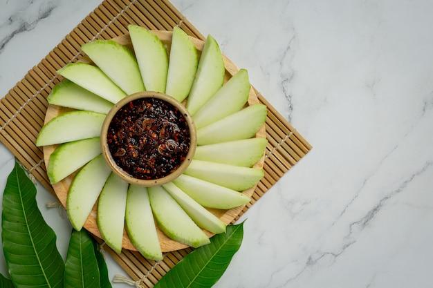 Frische grüne mango mit süßer fischsauce, die auf weiße oberfläche eintaucht