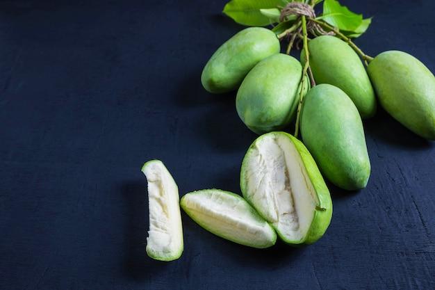 Frische grüne mangofrucht auf einem holztisch