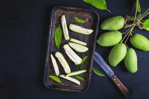 Frische grüne mangofrucht geschnitten auf einem behälter