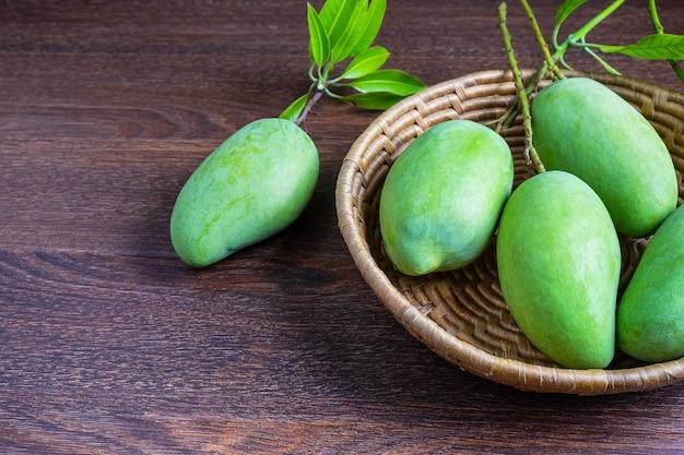 Frische grüne mangofrucht in einem hölzernen korb