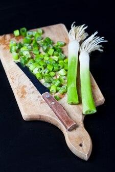 Frische grüne organische gehackte zwiebeln und messer auf einem schneidebrett