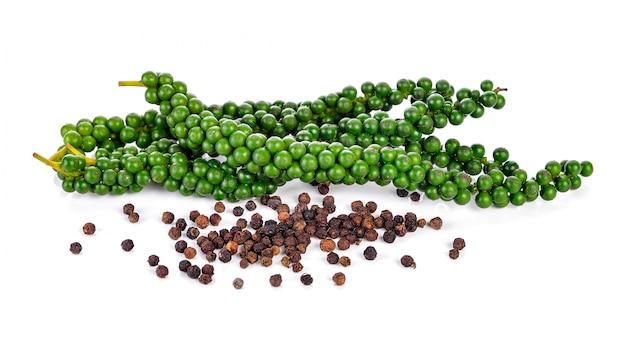 Frische grüne pfefferkörner und schwarze pfefferkörner getrennt auf weiß