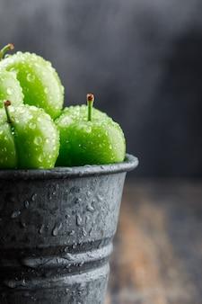 Frische grüne pflaumen in einem mini-eimer auf hölzerner und nebliger wand, nahaufnahme. Kostenlose Fotos