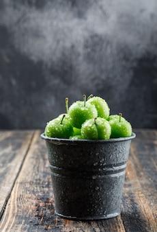 Frische grüne pflaumen in einer mini-eimerseitenansicht auf hölzerner und nebliger wand