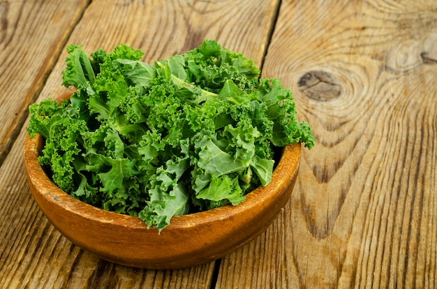Frische grüne sabellica-blätter auf holzuntergrund, gesunde bio-lebensmittel. studiofoto