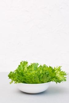 Frische grüne salatblätter in einer schüssel auf dem tisch. gesundes essen. speicherplatz kopieren. vertikale ansicht