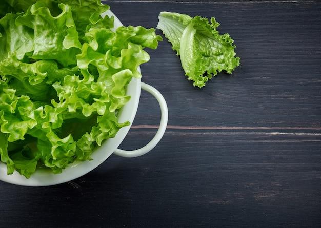 Frische grüne salatblätter in weißem sieb auf dunklem holzküchentisch, draufsicht