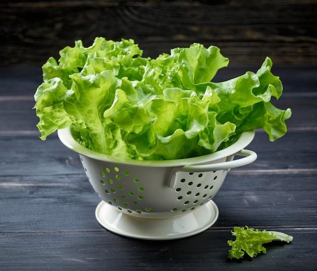Frische grüne salatblätter in weißem sieb auf dunklem holzküchentisch