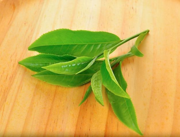 Frische grüne teeblätter auf holz