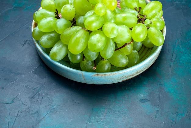 Frische grüne trauben der halben draufsicht milde saftige früchte innerhalb platte auf dem dunkelblauen schreibtisch.