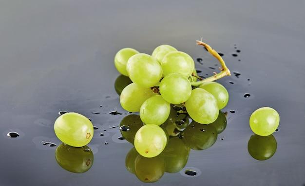 Frische grüne trauben mit wasser fällt auf einen grauen hintergrund