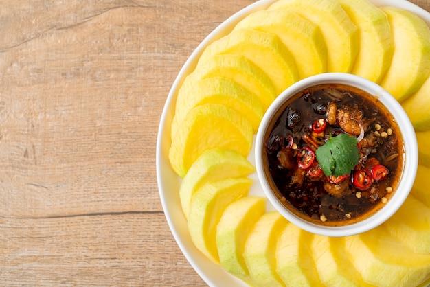 Frische grüne und goldene mango mit süßer fischsauce nach asiatischer art