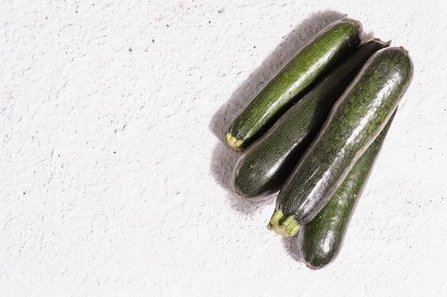 Frische grüne zucchini. reifes gemüse ernten. trendiges hartes licht, dunkler schatten, weißer kitthintergrund, draufsicht