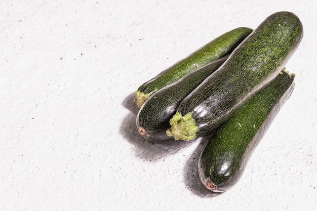 Frische grüne zucchini. reifes gemüse ernten. trendiges hartes licht, dunkler schatten, weißer kitthintergrund, kopierraum