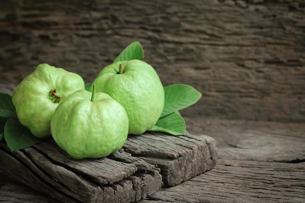 Frische guave mit grünen blättern auf hölzernem hintergrund.