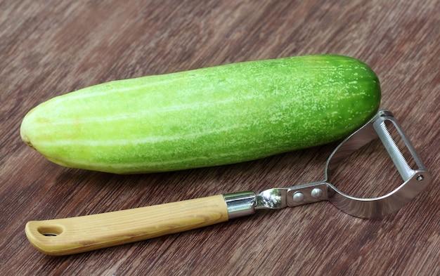 Frische gurke mit sparschäler auf holzoberfläche
