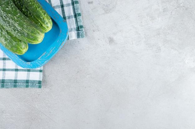 Frische gurken auf einem blauen brett auf einer tischdecke. foto in hoher qualität