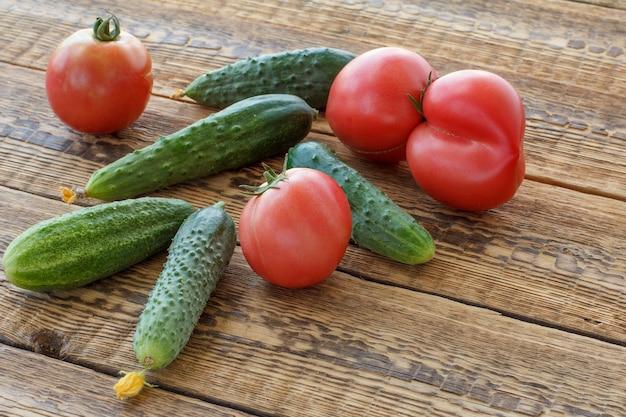 Frische gurken und tomaten im garten auf alten holzbrettern gepflückt. frisches gemüse. ansicht von oben.