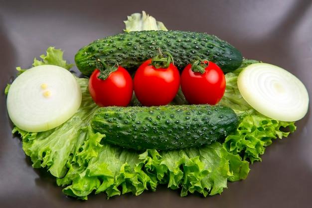 Frische gurken und tomaten und salat auf einem grauen teller. vitamine und leichtes frühstück