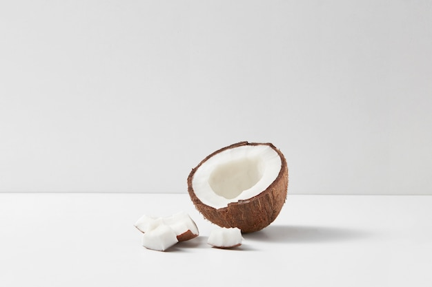Frische hälfte der reifen organischen tropischen kokosnussfrucht auf einem hellgrauen duotonen hintergrund mit weichen schatten und kopierraum. vegetarisches konzept.