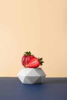 Frische hässliche erdbeere auf stand auf einem modernen papierhintergrund in blau und beige. nahansicht. vertikales stillleben mit bio-öko-erdbeere.
