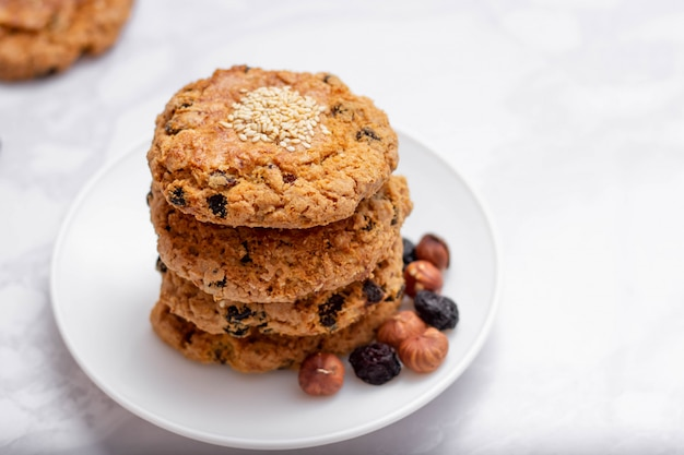 Frische haferflocken bröckelige kekse auf einem teller mit nüssen und rosinen