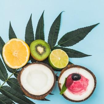 Frische halbierte orange; kiwi; zitrone und kokosnuss mit eiscreme auf grünen blättern gegen blauen hintergrund