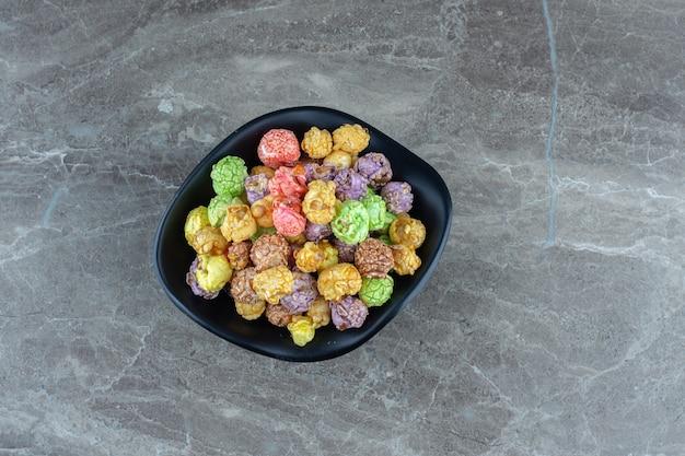 Frische hausgemachte bunte bonbons in schwarzer schüssel.