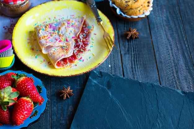 Frische hausgemachte crepes serviert auf einem teller mit erdbeeren und heidelbeeren